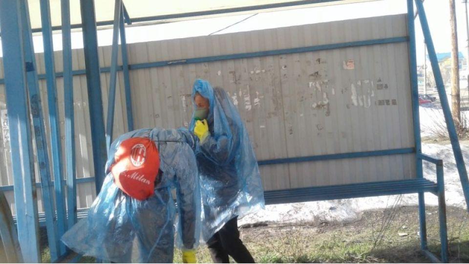 Коммунальщики в дождевиках обрабатывают остановки в Змеиногорске