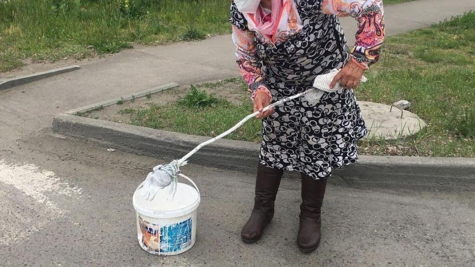 Жительница Бийска рисует разметку на дороге
